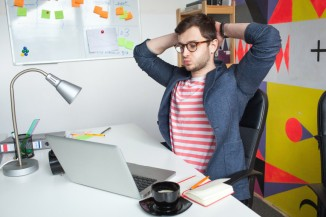 Stressed young male in modern office with laptop